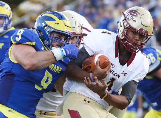 Delaware's Troy Reeder claws at the ball as he tackles Elon's Jalen Greene in the fourth quarter of the Blue Hens' 28-16 win at Delaware Stadium in 2018.