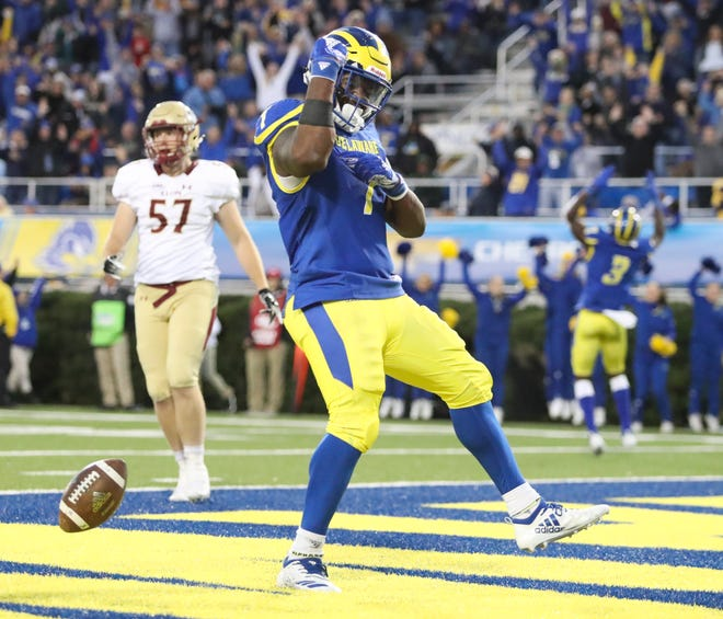 Delaware running back Kani Kane flexes his muscles after a two yard run accounting for the final score in the fourth quarter of the Blue Hens' 28-16 win against Elon at Delaware Stadium Saturday.