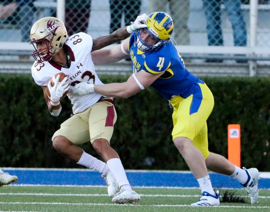 Delaware's Colby Reeder (right) holds onto Elon's Corey Joyner and prevents a first down on third-and-seven in the third quarter of the Blue Hens' 28-16 win at Delaware Stadium Saturday. Elon settled for a field goal.