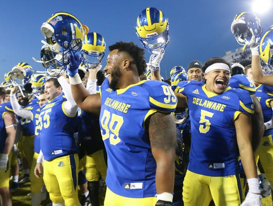 Delaware's Cam Kitchen (99) and Gene Coleman II (5) join with the band and team during the fight song after the Blue Hens' 28-16 win at Delaware Stadium Saturday.