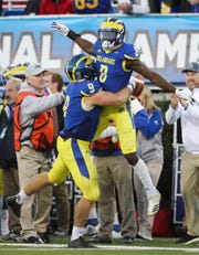 Delaware's Tenny Adewusi (8) and Troy Reeder celebrate a stop and forced Elon punt in the fourth quarter of the Blue Hens' 28-16 win at Delaware Stadium.