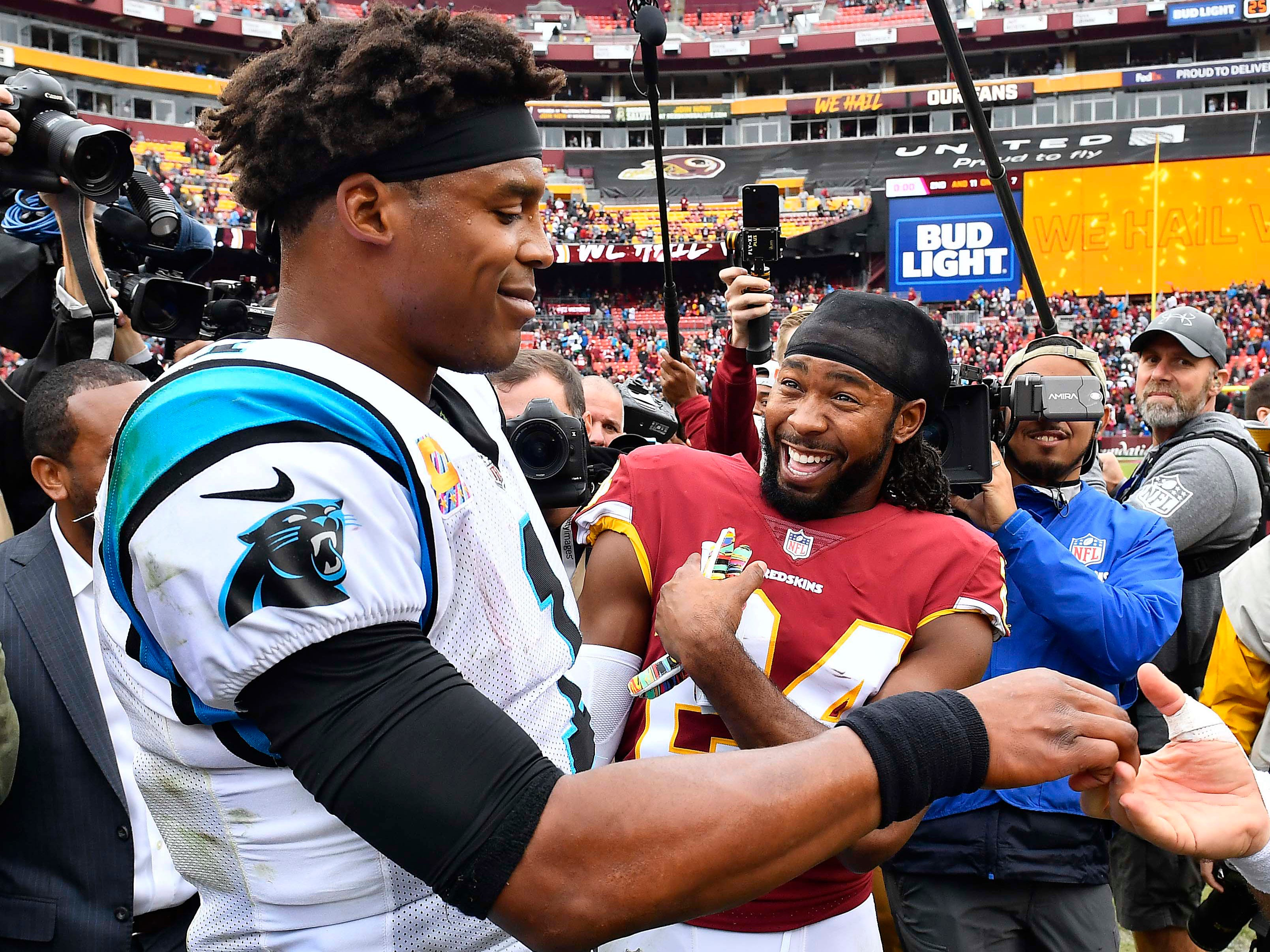 Washington Redskins cornerback Josh Norman talks with former teammate and Carolina Panthers quarterback Cam Newton after their game at FedEx Field. The Redskins won, 23-17.