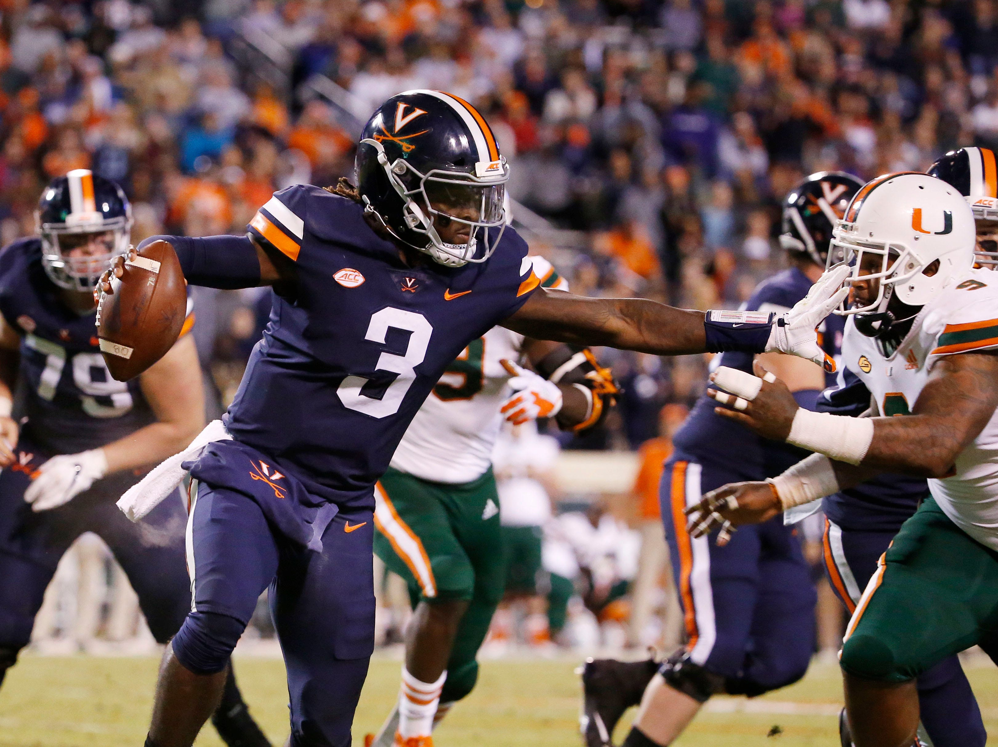 Virginia Cavaliers quarterback Bryce Perkins (3) throws a stiff-arm against the Miami Hurricanes during the second quarter at Scott Stadium.