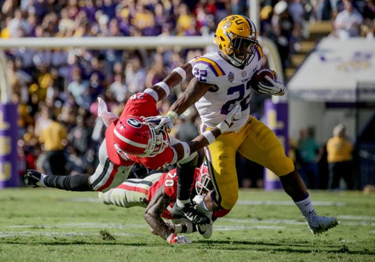 LSU running back Clyde Edwards-Helaire breaks away from Georgia defensive back Tyrique McGhee (26) and defensive back J.R. Reed (20) during the second quarter at Tiger Stadium.