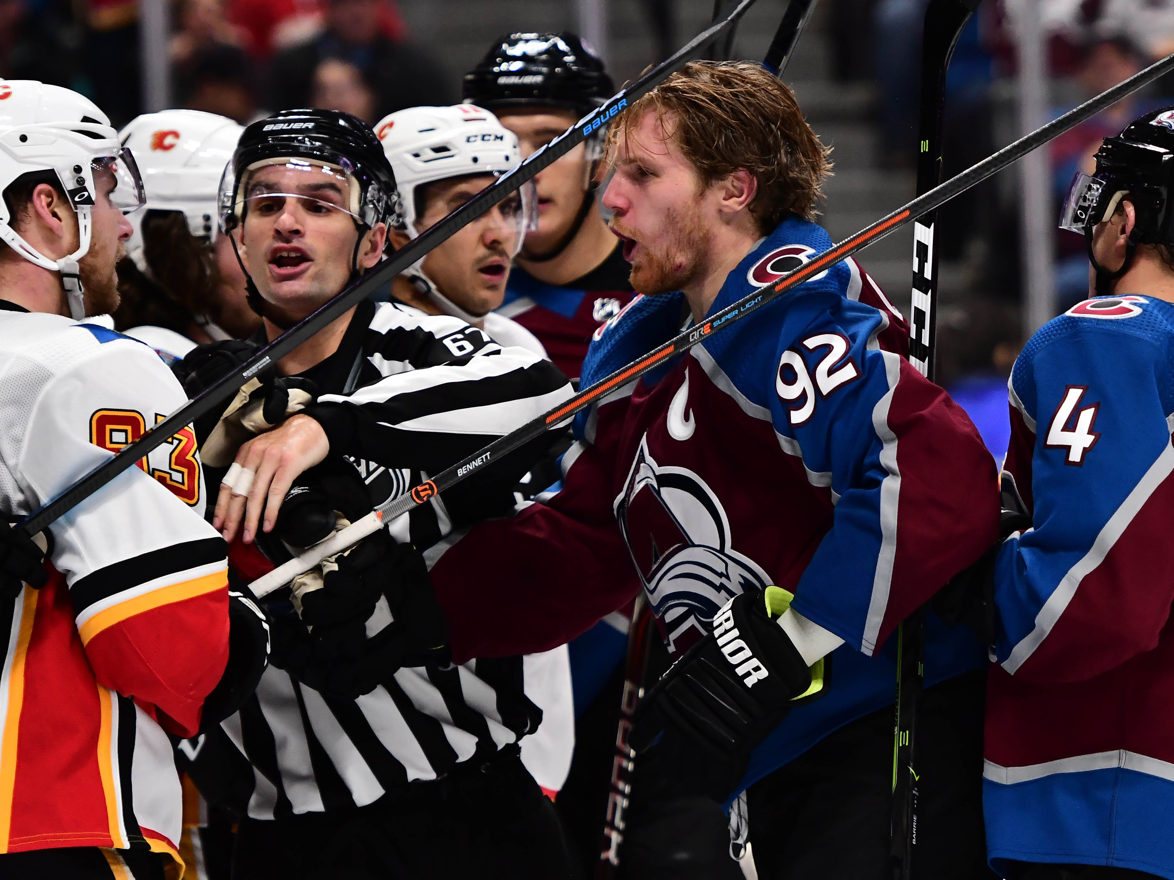 Oct 13: NHL linesman Travis Gawryletz (67) breaks up a fight between Avalanche left wing Gabriel Landeskog (92) and Flames center Sam Bennett (93)