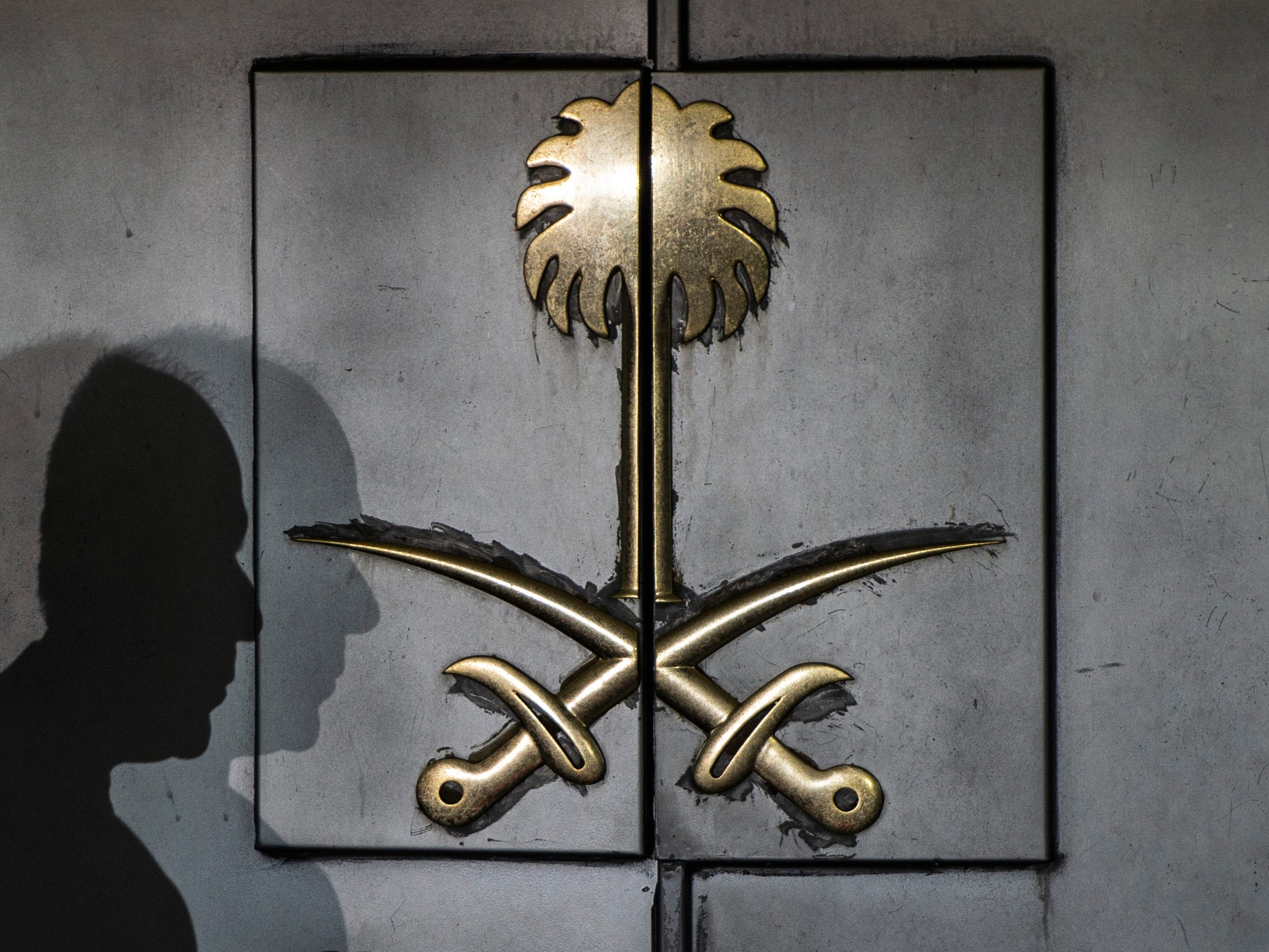 The shadow of a security guard is seen on the entrance door of the Saudi Arabia's consulate in Istanbul, Oct. 12, 2018.