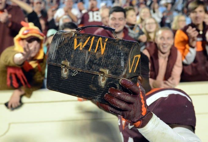 Virginia Tech Hokies defensive back Reggie Floyd (21) holds up a lunch pail after a win against the North Carolina Tar Heels at Kenan Memorial Stadium.
