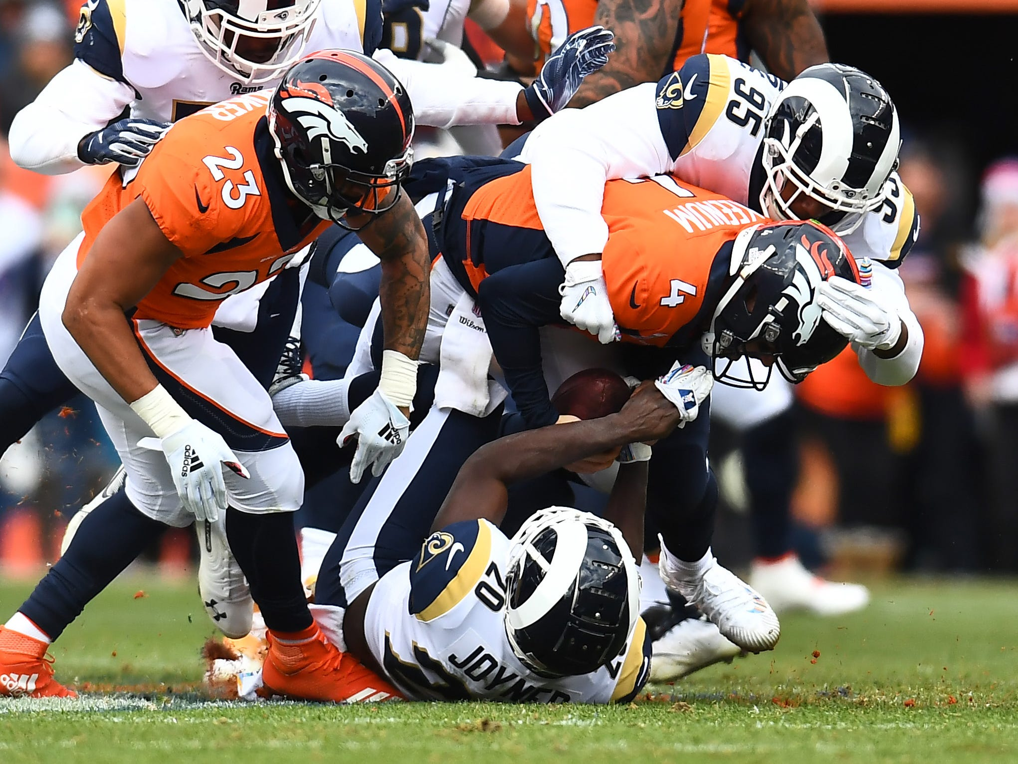 Los Angeles Rams safety Lamarcus Joyner (20) and defensive lineman Ethan Westbrooks (95) combine to sack Denver Broncos quarterback Case Keenum in the second quarter at Broncos Stadium at Mile High.