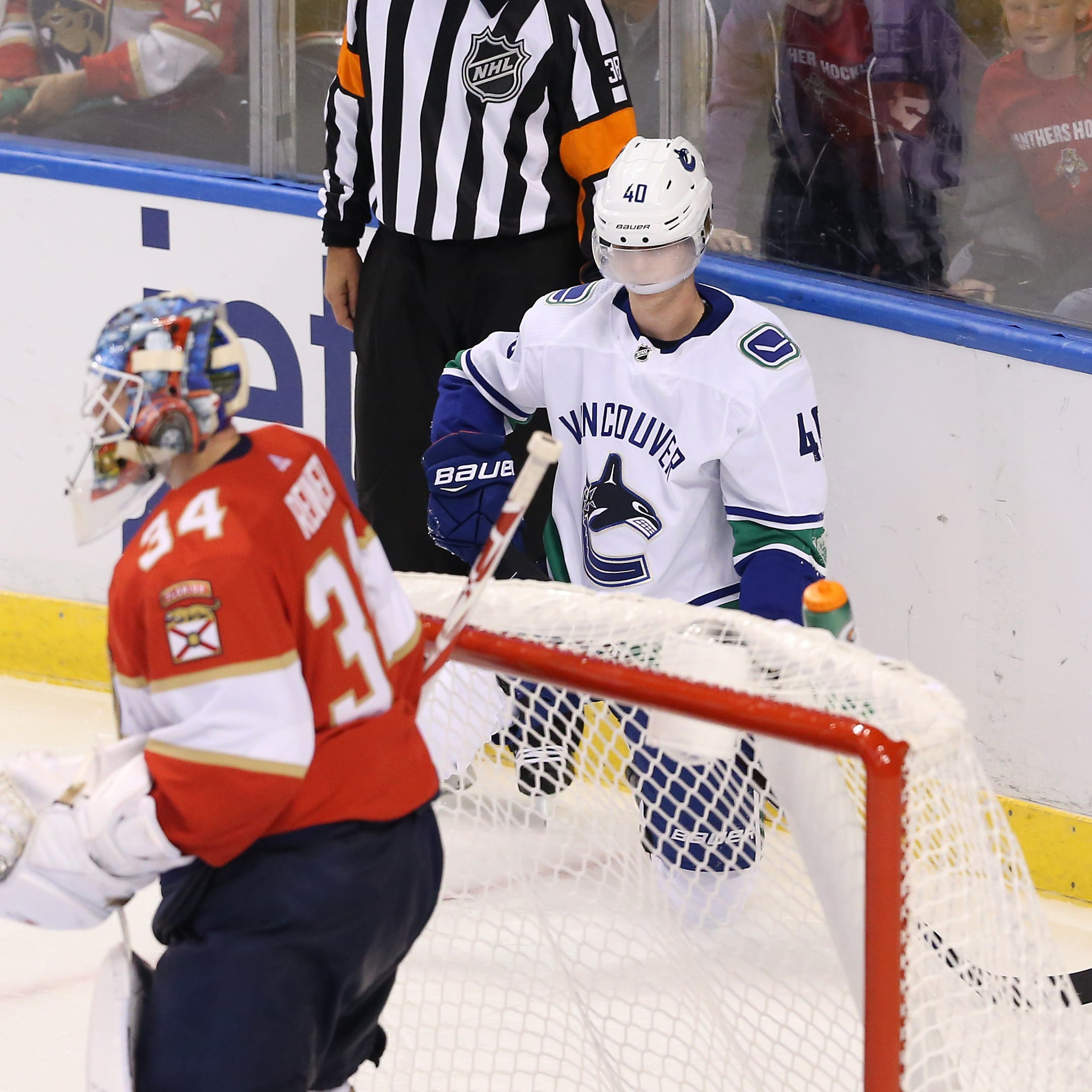 Canucks center Elias Pettersson tries to compose himself after a hard hit by Panthers defenseman Mike Matheson.