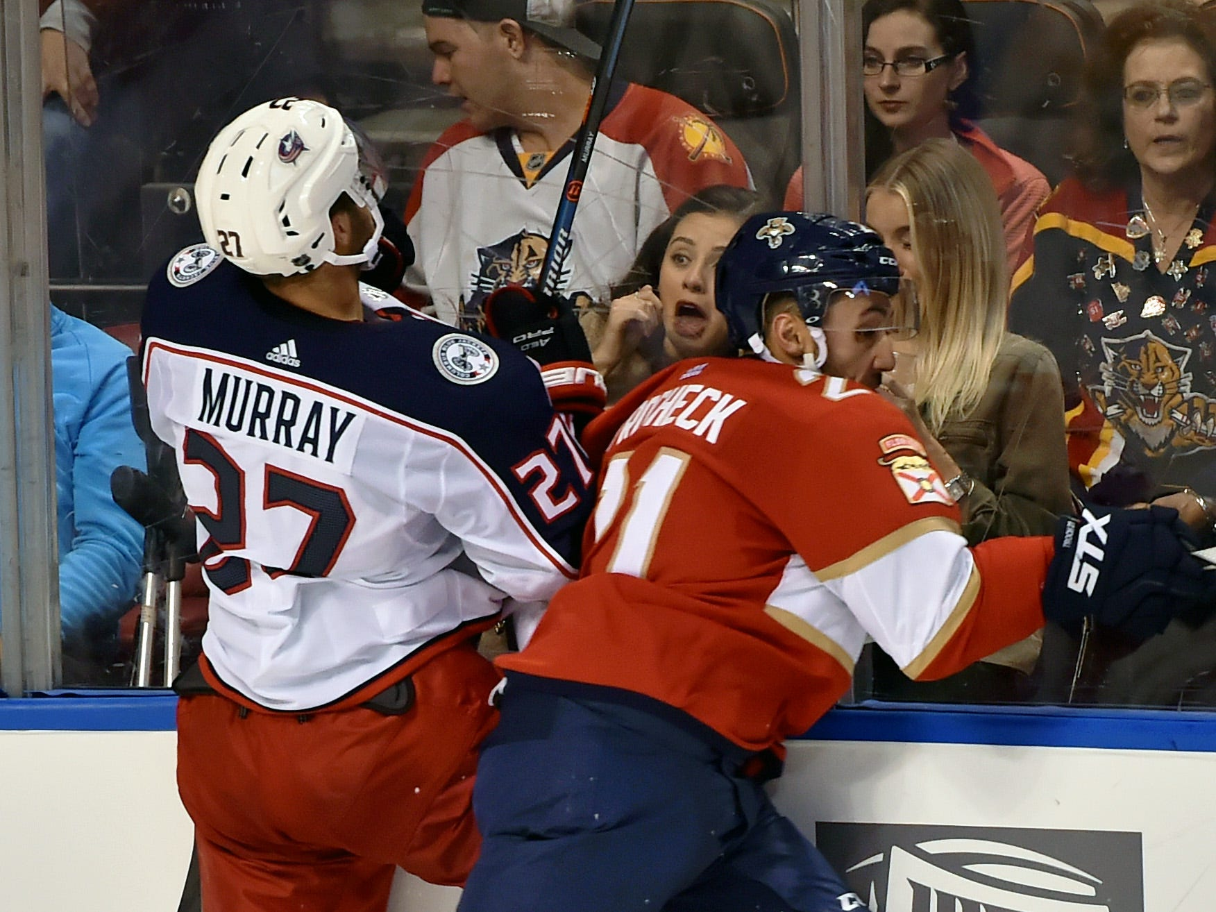 Oct. 11: Columbus Blue Jackets defenseman Ryan Murray (27) is checked into the boards by Florida Panthers center Vincent Trocheck (21), surprising a fan during the third period at BB&T Center in Sunrise, Fla.