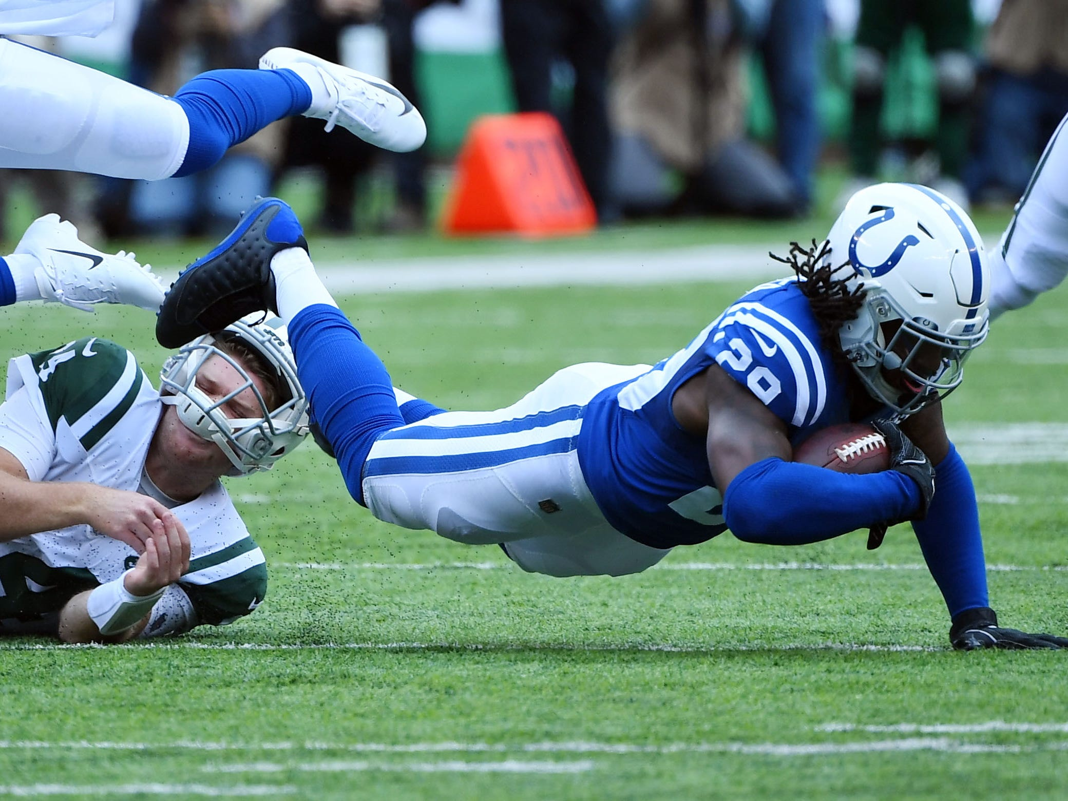 Indianapolis Colts safety Malik Hooker (29) is tackled by New York Jets quarterback Sam Darnold (14) after an interception in the second quarter at MetLife Stadium.