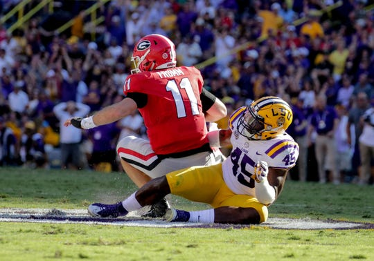 Georgia quarterback Jake Fromm is sacked by LSU linebacker Michael Divinity Jr. during the second half at Tiger Stadium.