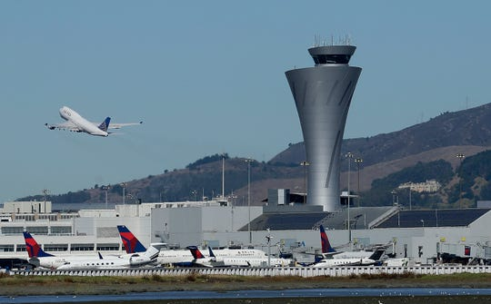 In this Oct. 24, 2017 file photo, the air traffic control tower is in sight as a plane takes off from San Francisco International Airport in San Francisco. The National Transportation Safety Board issued a final report Thursday, Oct. 11, 2018  on the July 2017 close call in which an Air Canada jet nearly crashed into planes lined up on the ground at San Francisco International Airport.