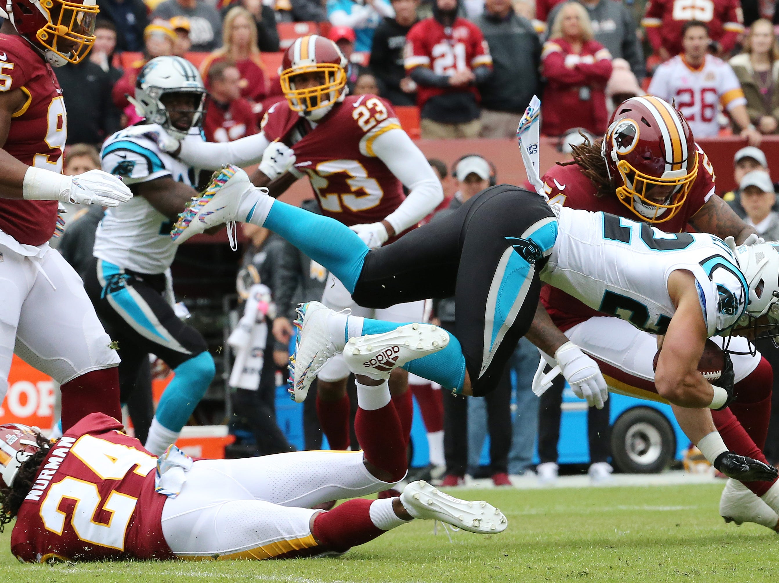 Carolina Panthers running back Christian McCaffrey (22) is tackled by Washington Redskins cornerback Josh Norman (24) in the first quarter at FedEx Field.
