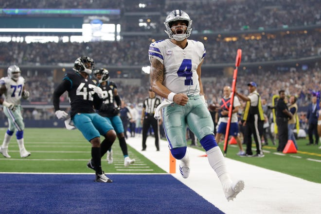 Dallas Cowboys quarterback Dak Prescott reacts after running for a touchdown against the Jacksonville Jaguars in the first quarter at AT&T Stadium.