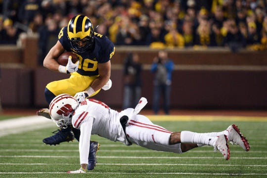Michigan Wolverines wide receiver Oliver Martin (80) is tackled by Wisconsin Badgers cornerback Deron Harrell (8) during the first quarter at Michigan Stadium.