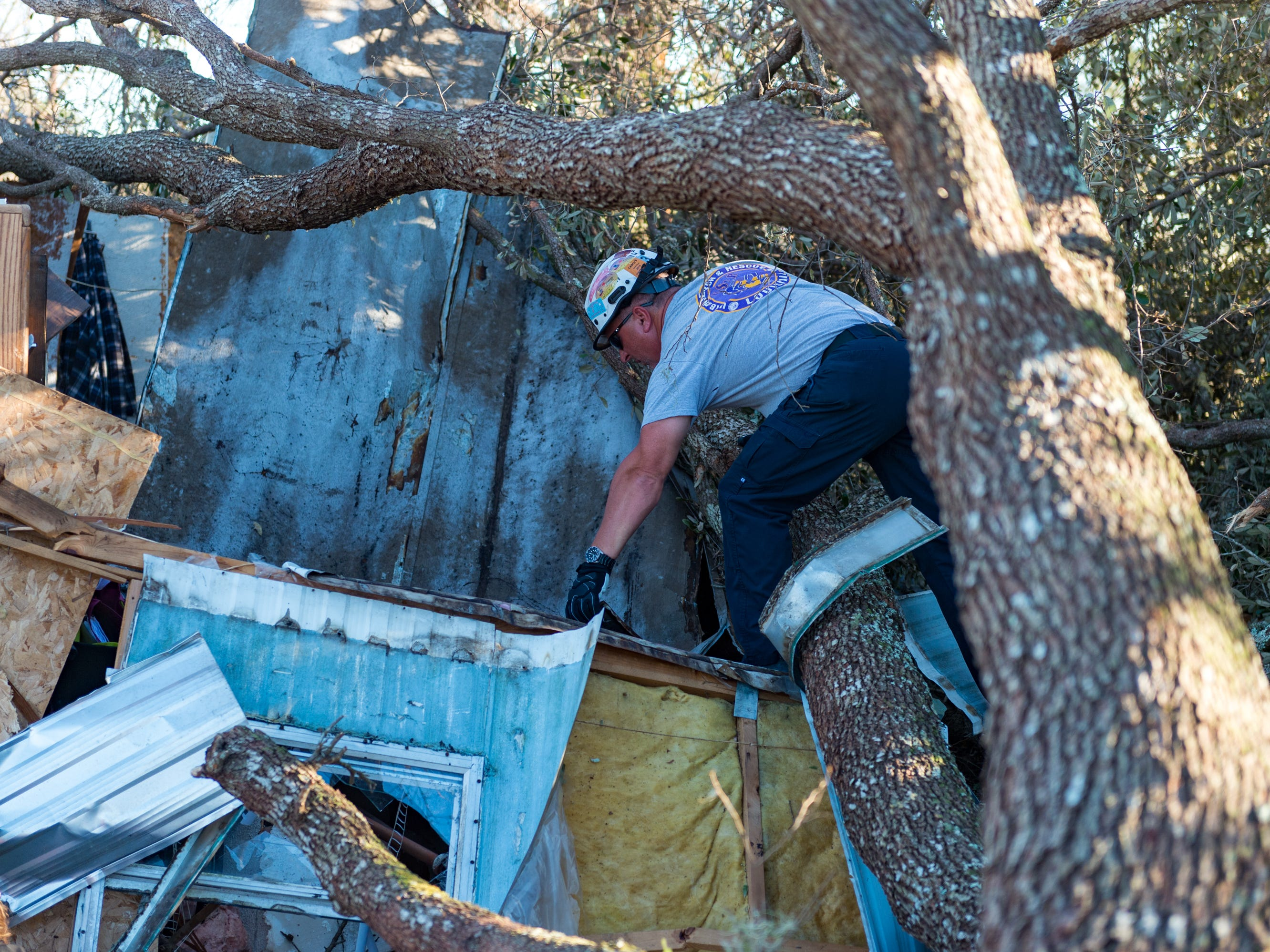 Rescue Tech Jason Graphia from the The Louisiana Urban Search and Rescue Task Force, climbs over debris to search a house that was destroyed by a tree near Panama City in the aftermath of Hurricane Michael, Oct. 13, 2018.