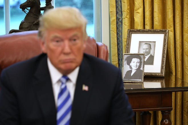 President Donald Trump and photographs of Fred and Mary Trump.