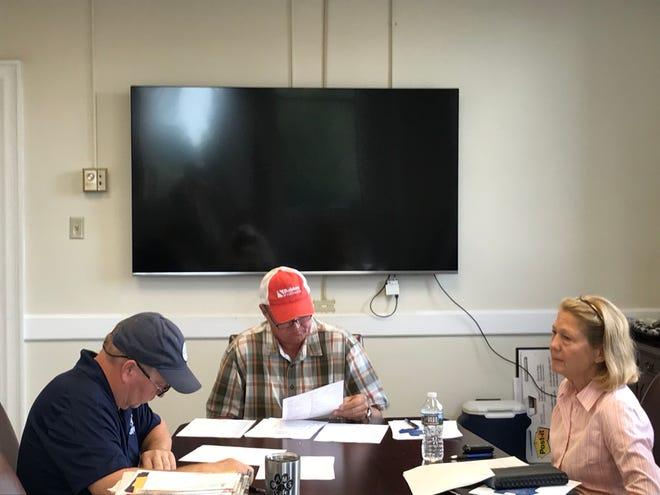 "County Councilman Ray Graham, left, council Chairman Tommy Dunn and Councilwoman Cindy Wilson sit near a newly purchased 82-inch Samsung ""smart"" TV in a conference room at the historic Anderson County Courthouse in downtown Anderson."