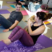Brice and Lindsey Trickey take part in a yoga class at the Fox Valley Humane Association in Appleton on Oct. 13.