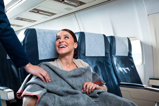 Bring your own blanket onto the plane.  Buy one that is warm yet lightweight and not bulky.