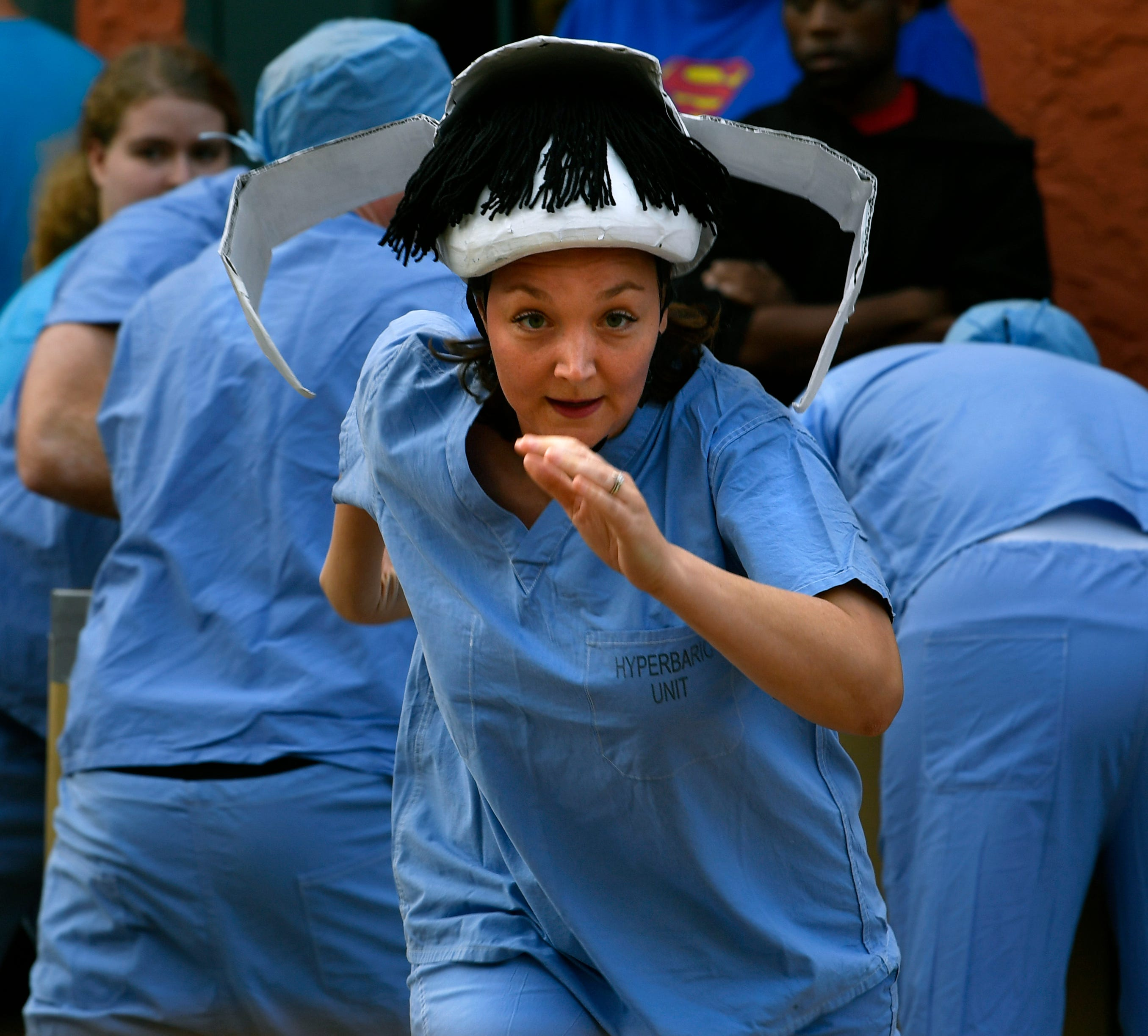 Mary Horban runs to the gurney that will carry her as the rest of her team from Hendrick Medical Center finishes sorting boxes during The Great Gurney Race Thursday during ArtWalk.