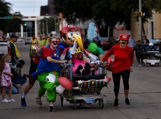 Hardin-Simmons University physician assistants run their decorated gurney toward the finish line on Cypress St. Thursday Oct. 11, 2018. Part of ArtWalk, the Great Gurney Race benefitted Global Samaritan Resources.