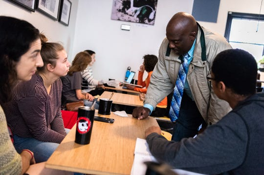Quentin Miller, a candidate for Buncombe County Sheriff, talks with UNCA students, Arielle Jacobsen, 18, and Isaiah Green, also 18, at Pennycup Coffee on Market Street, Oct. 11, 2018. Miller, who was an Asheville police officer for 24 years, is a candidate for Buncombe County Sheriff.