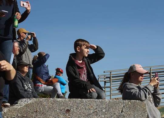 People look on as the USS John C. Stennis passes Bachmann Park after departing Naval Base Kitsap-Bremerton on Monday.