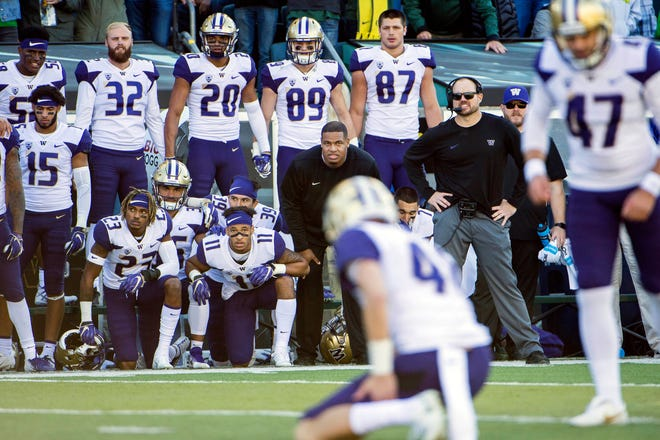Washington players and coaches watch from the sidelines as kicker Peyton Henry lines up for a field goal attempt on Saturday in Eugene. Henry missed the kick at the end of regulation, and the Huskies lost in overtime, 30-27, to Oregon.