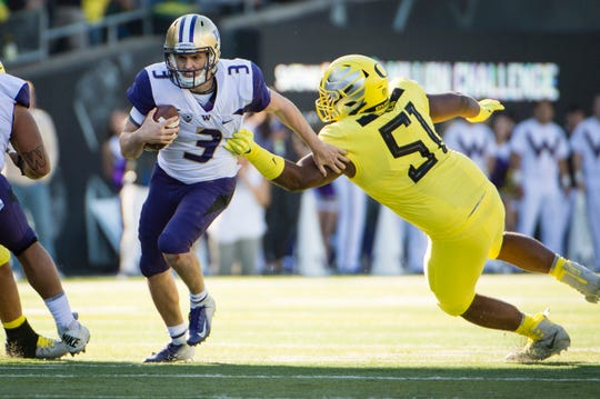 Huskies quarterback Jake Browning breaks away from Oregon Ducks defensive lineman Gary Baker (51) during the second half at Autzen Stadium. The Ducks won in overtime 30-27.