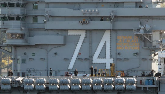 Sailors stand on the deck in front of the 74 as the USS John C. Stennis departs Naval Base Kitsap-Bremerton on Monday.
