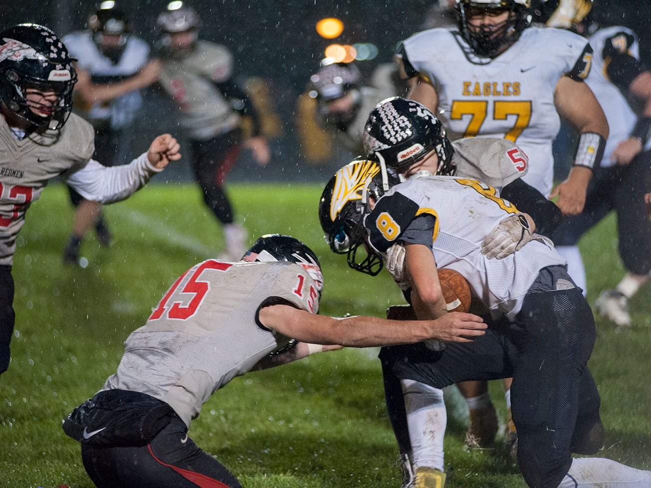 Colonel Crawford's Colton Rowland is tackled by Bucyrus' Keaton Naufzinger and Hastin Zier.