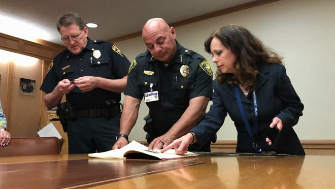 Corpus Christi police Commander John Houston (from left), Chief Mike Markle and Celeste Hogan, a volunteer at the department, look at a police yearbook from the 1920s at the department headquarters on Monday, Oct. 15, 2018.