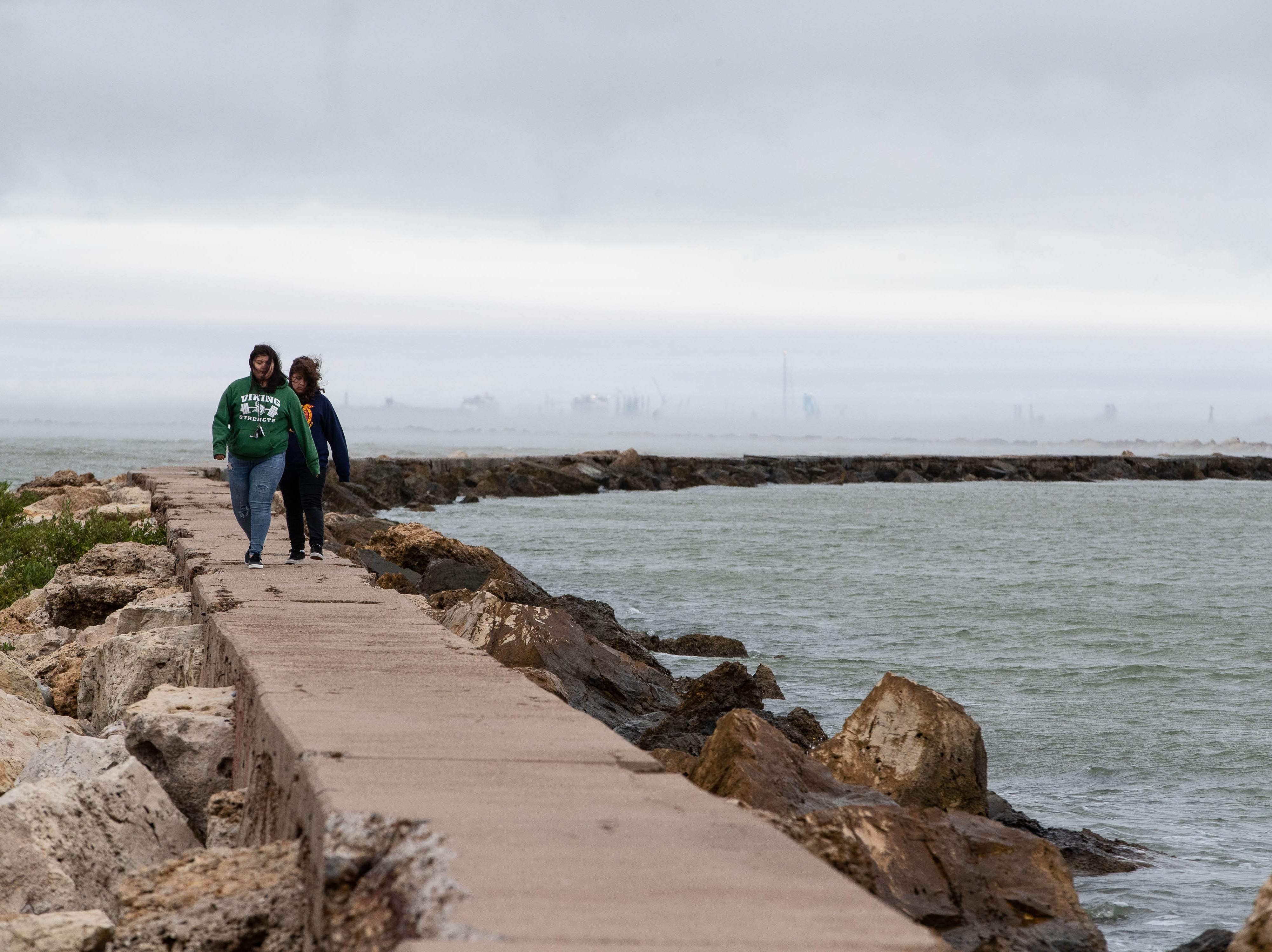 Jaynize Tey and Celeste Rodriguez walk along the jetty in downtown Corpus Christi as a cold front roles in to the Coastal Bend on Monday, Oct. 15, 2018