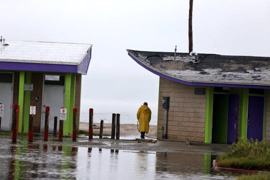 A city of Corpus Christi worker cleans North Beach bathrooms as the rod and parking lot it flooded Monday.