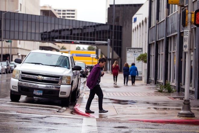 People rush to their destinations in uptown as a cold front and rain moved through the area on Monday, October 15, 2018.