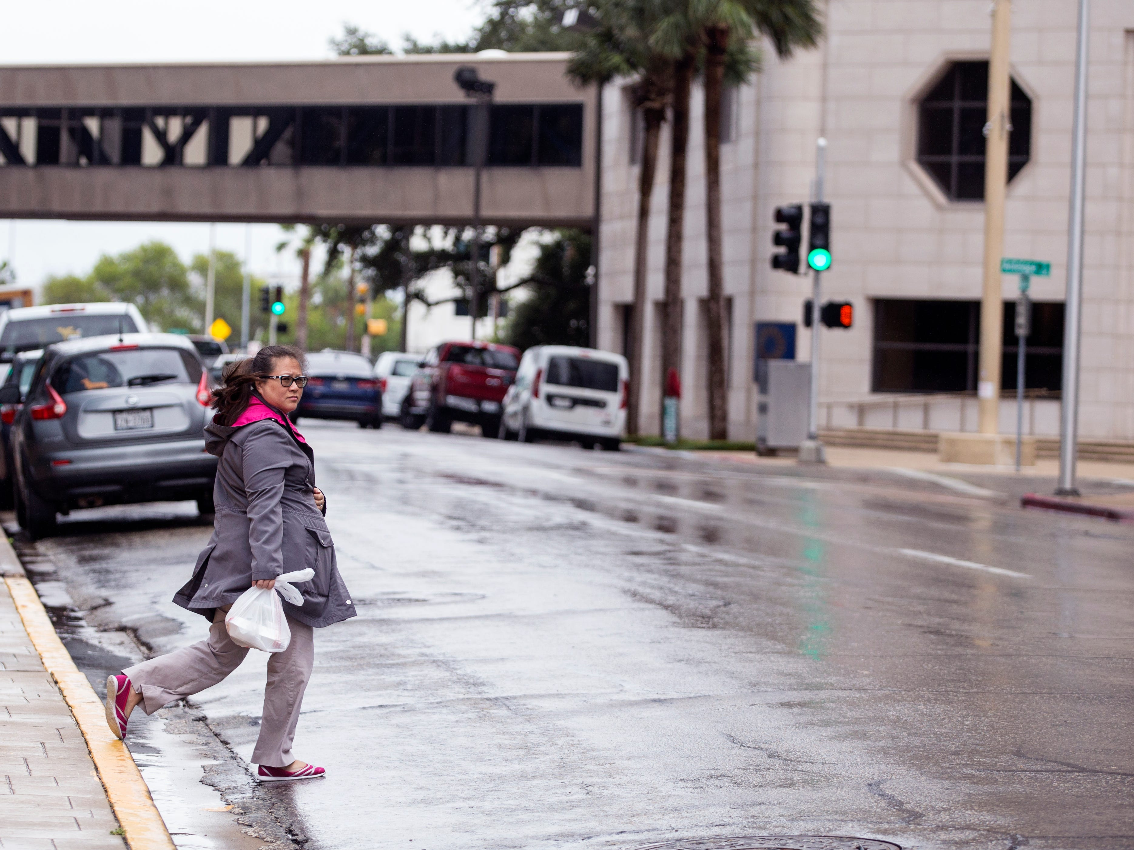 A woman rushes to her destination in uptown as a cold front and rain moved through the area on Monday, October 15, 2018.