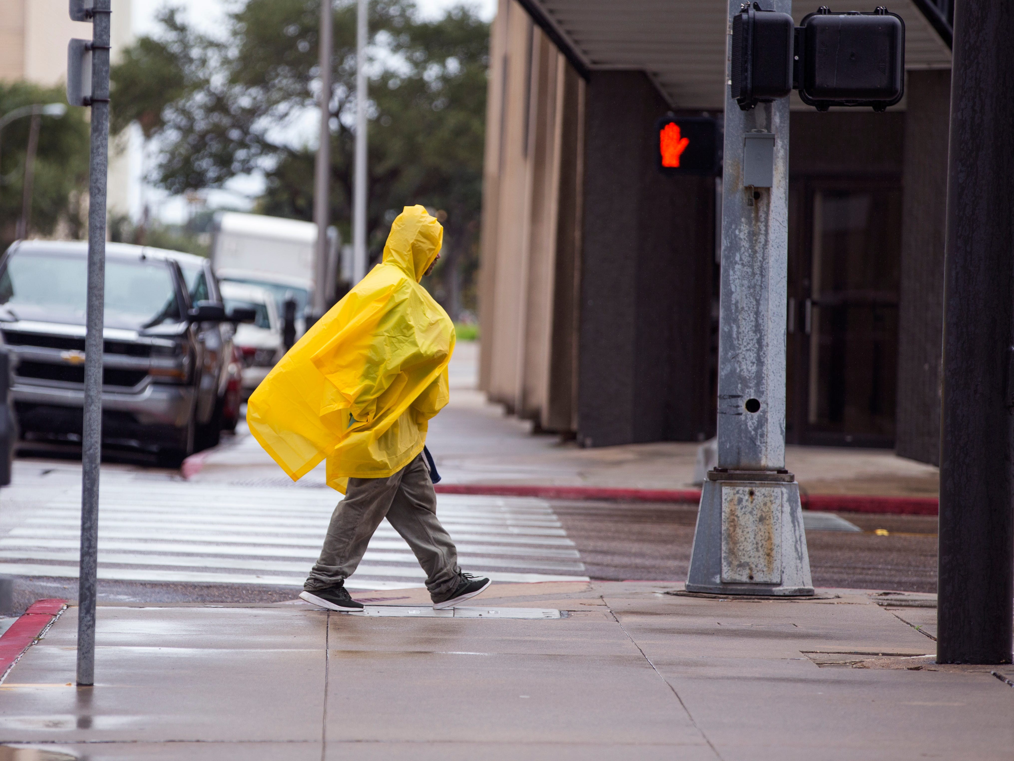 A man tries to stay dry and warm in uptown as a cold front and rain moved through the area on Monday, October 15, 2018.