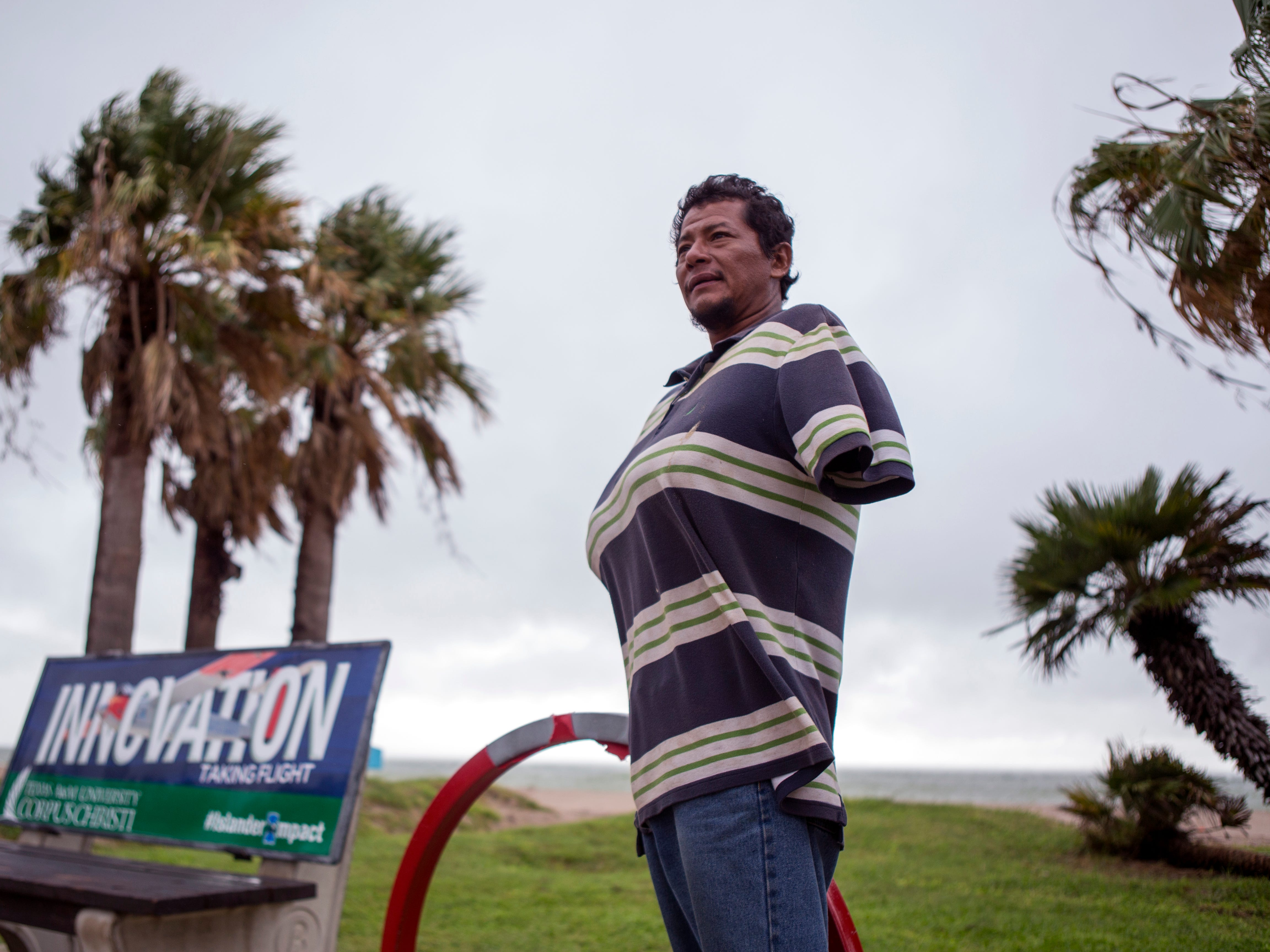 Carlo Garcia tucks his arms in his shirt to stay warm as he waits for a bus on North Beach on Monday, October 15, 2018. Cold temperatures moved through South Texas on Monday.