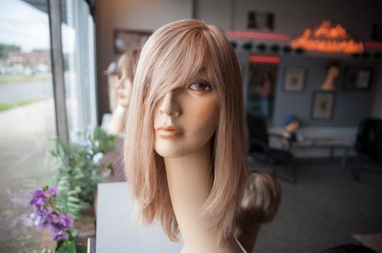 Wigs are displayed in the window of Hair for Now in Cherry Hill.  Hair for Now owner Nicole Gordon specifically helps those with hair problems, especially cancer patients.