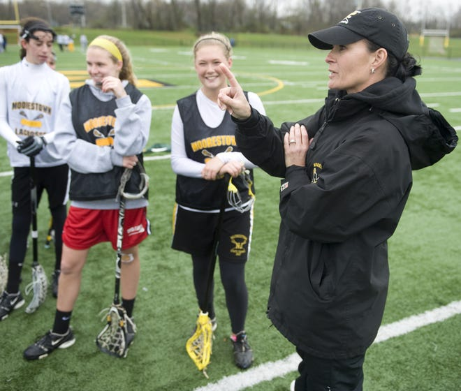 Moorestown girls' lacrosse coach Deanna Knobloch (right) instructs her players during a practice in 2010. Knobloch stepped down after 27 years and 15 state championships on Thursday.
