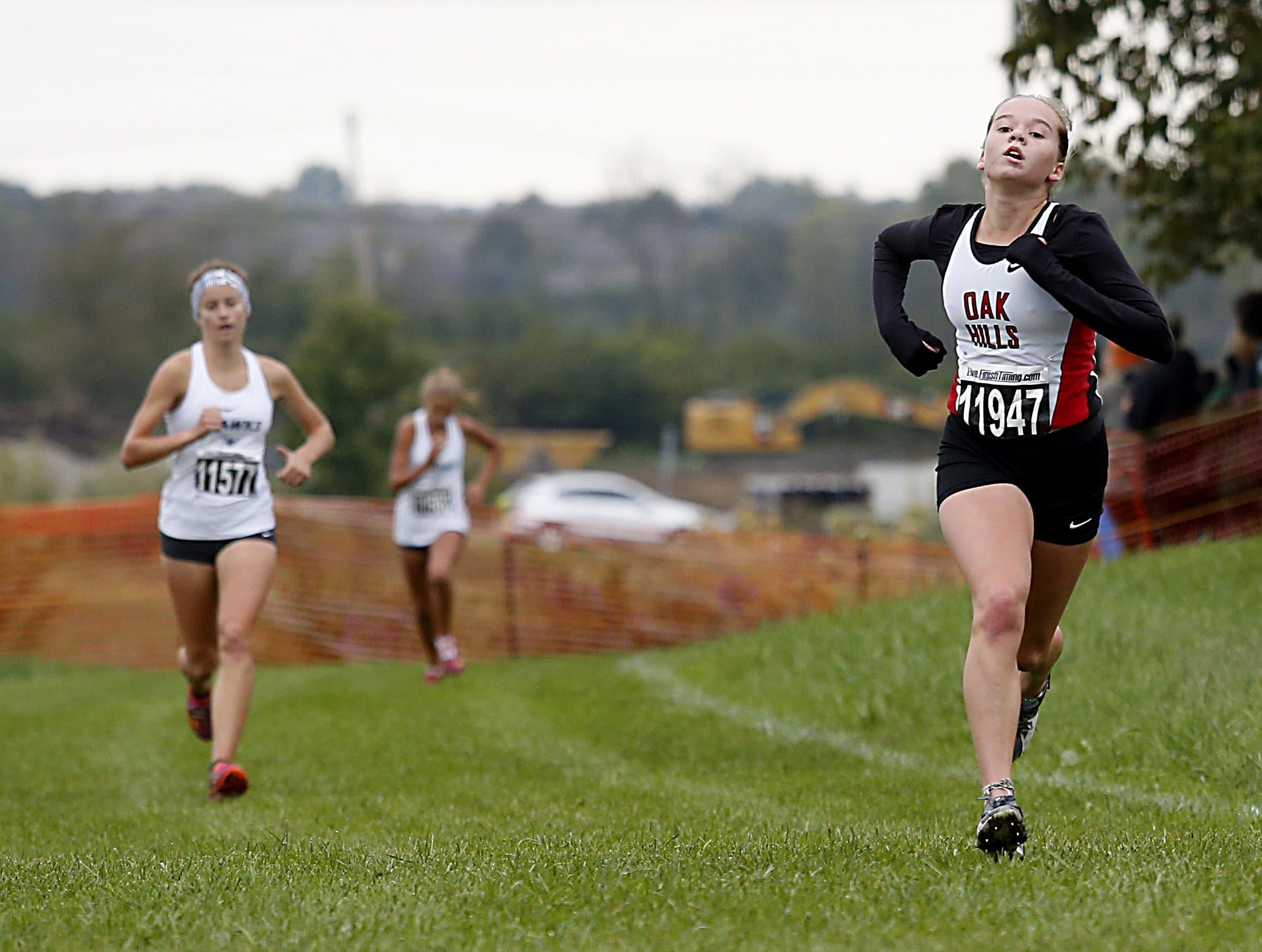 Oak Hills' Megan John crosses the finish in fifth during the Greater Miami Conference Girls and Boys Cross Country Championships at Voice of America Park in West Chester Saturday, Oct. 13, 2018.