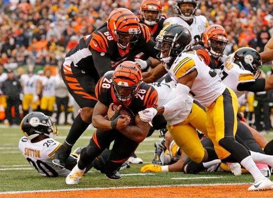 Cincinnati Bengals running back Joe Mixon (28) leans across the goal line for a go-ahead touchdown in the fourth quarter of the NFL Week 6 game between the Cincinnati Bengals and the Pittsburgh Steelers at Paul Brown Stadium in downtown Cincinnati on Sunday, Oct. 14, 2018. The Bengals and Steelers exchanged late touchdowns, with the Pittsburgh coming out on top, 28-21.