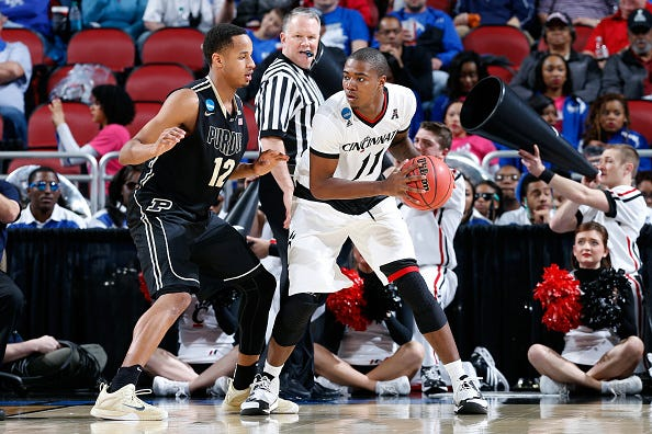 Gary Clark of the Cincinnati Bearcats controls the ball as Vince Edwards of the Purdue Boilermakers defends during the second round of the 2015 NCAA Men's Basketball Tournament at the KFC YUM! Center on March 19, 2015 in Louisville, Kentucky.