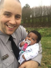 """North Carolina State Highway Patrol Trooper Kevin Barringer and """"M.A.,"""" the victim's then two-month-old daughter, who was rescued from the defendant's vehicle following a traffic stop the same day."""