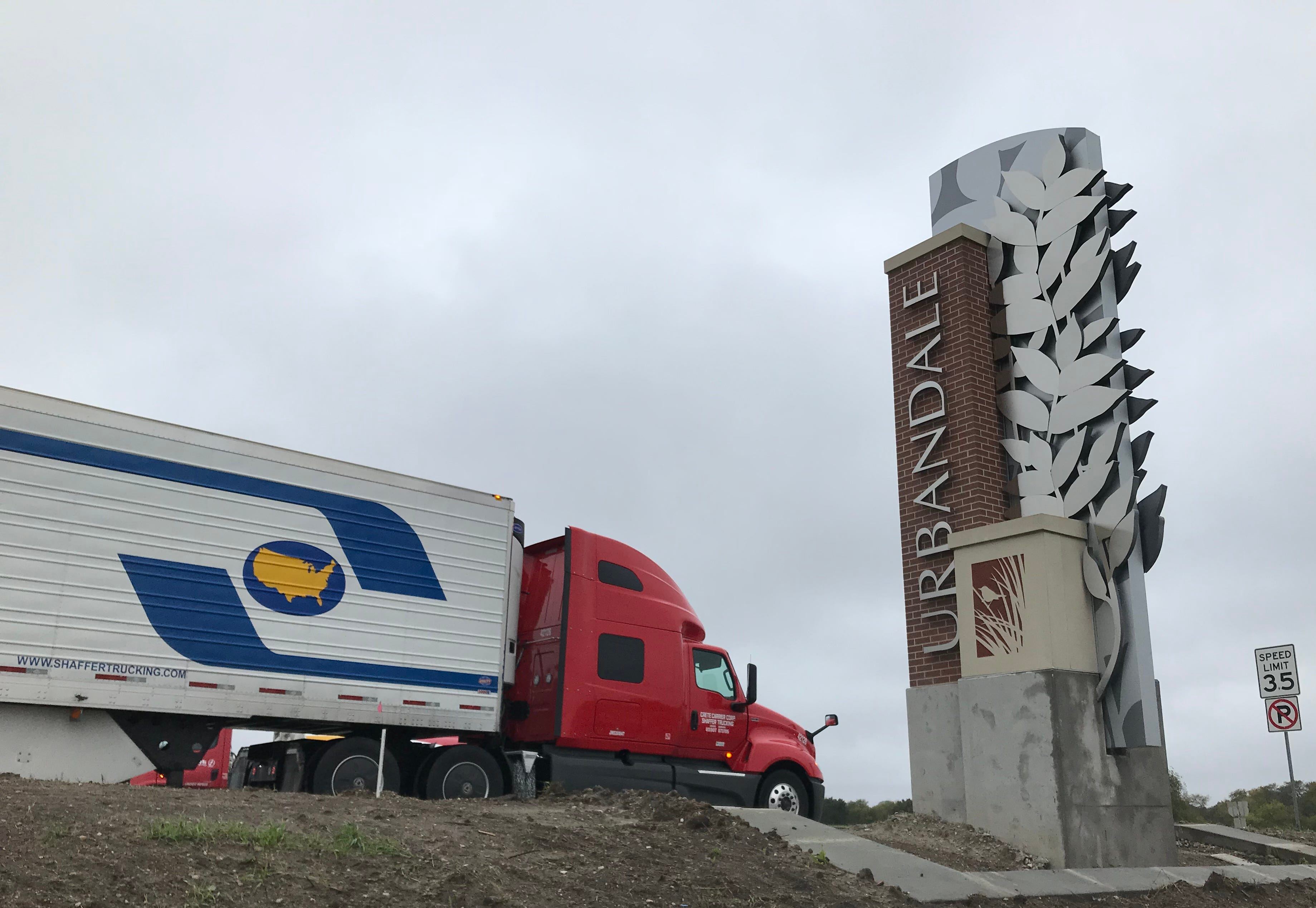 A semi passes one of Urbandale's new entrance signs on Douglas Avenue. The city is completing a beautification project along its entrance off Interstate 35/80 that includes four pillar-style monument signs.