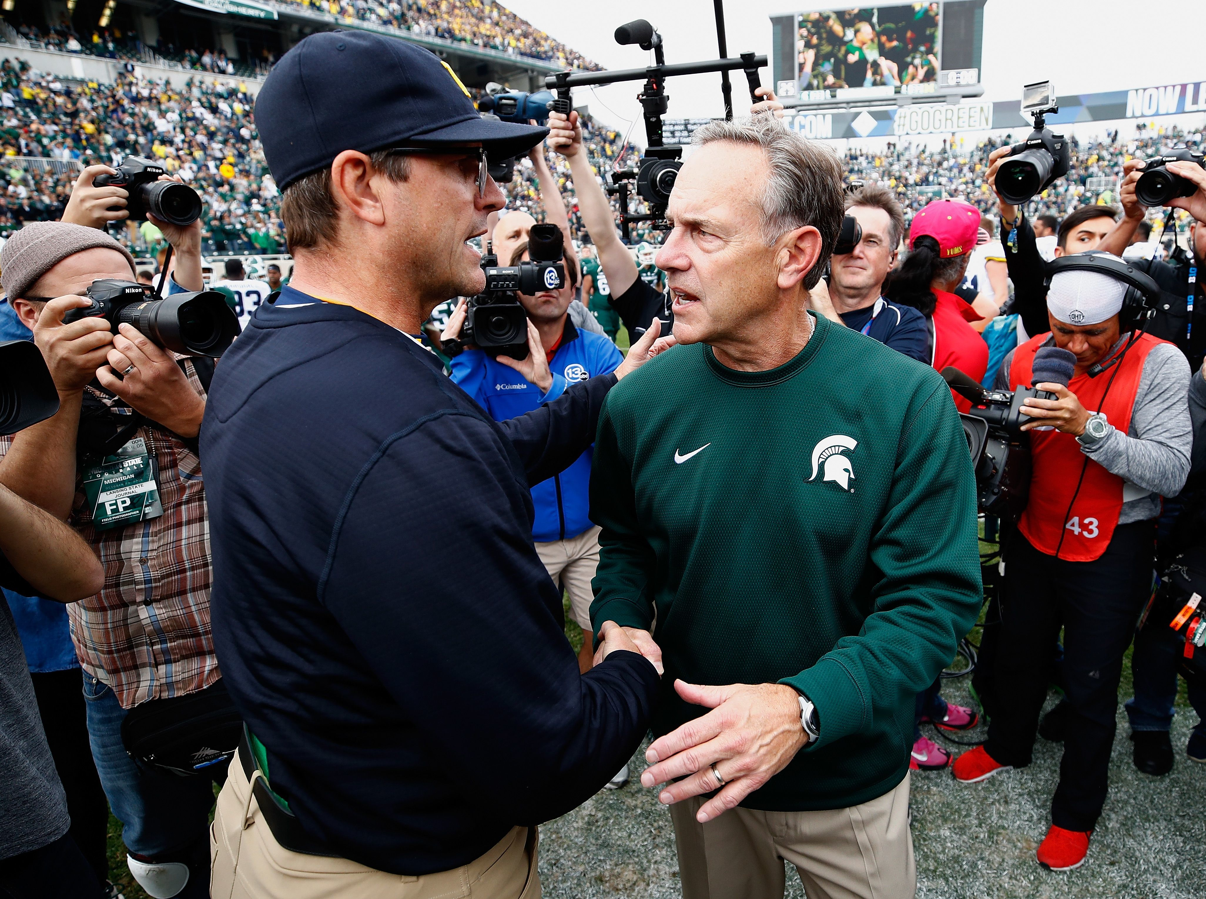 Coaches  Jim Harbaugh and Mark Dantonio, seen here after their 2016 match-up, are getting their teams ready to rumble again Saturday.