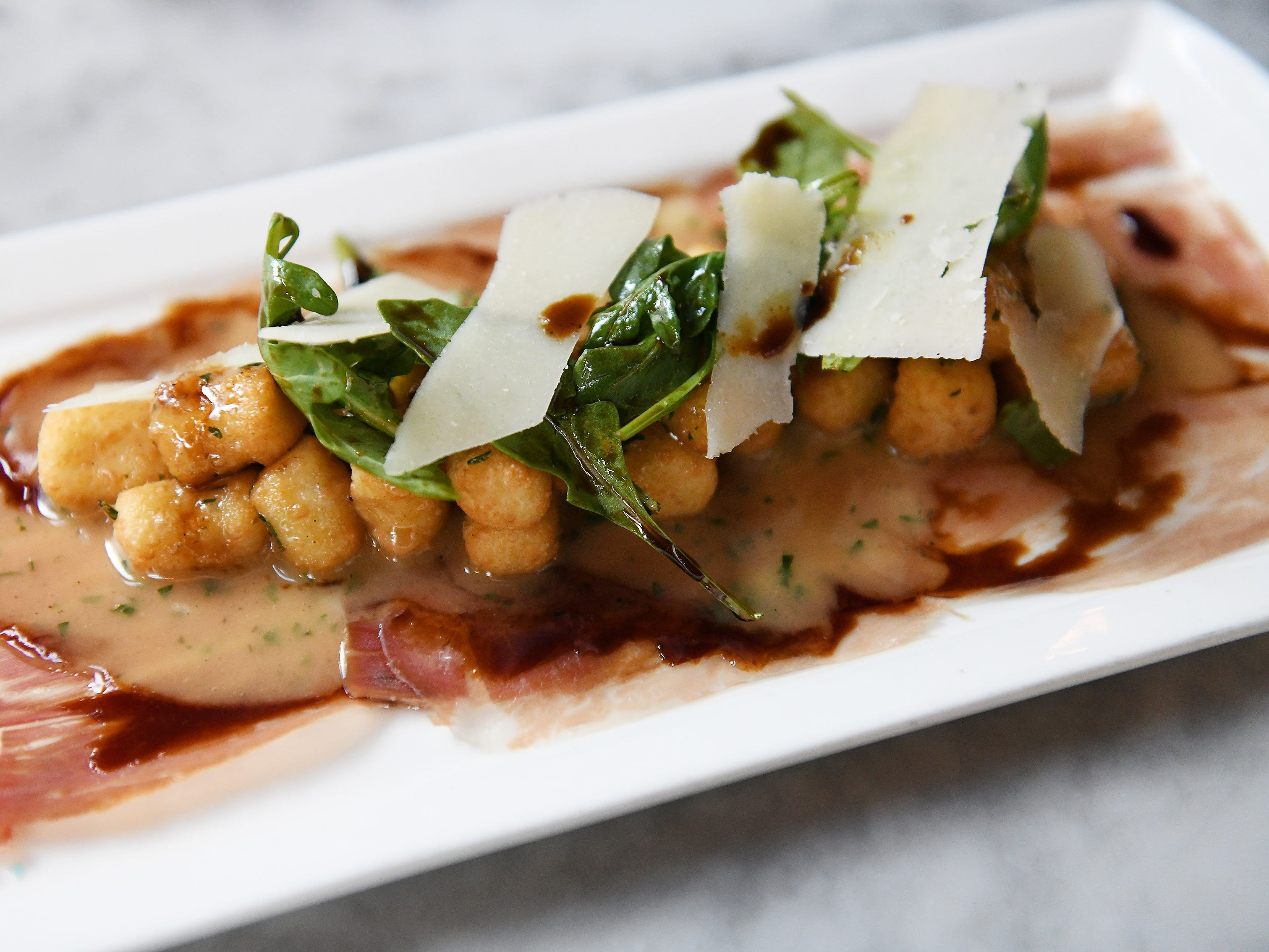 Parisian gnocchi with parma prosciutto, arugula, shaved Parmesan and saba. (Robin Buckson / The Detroit News)