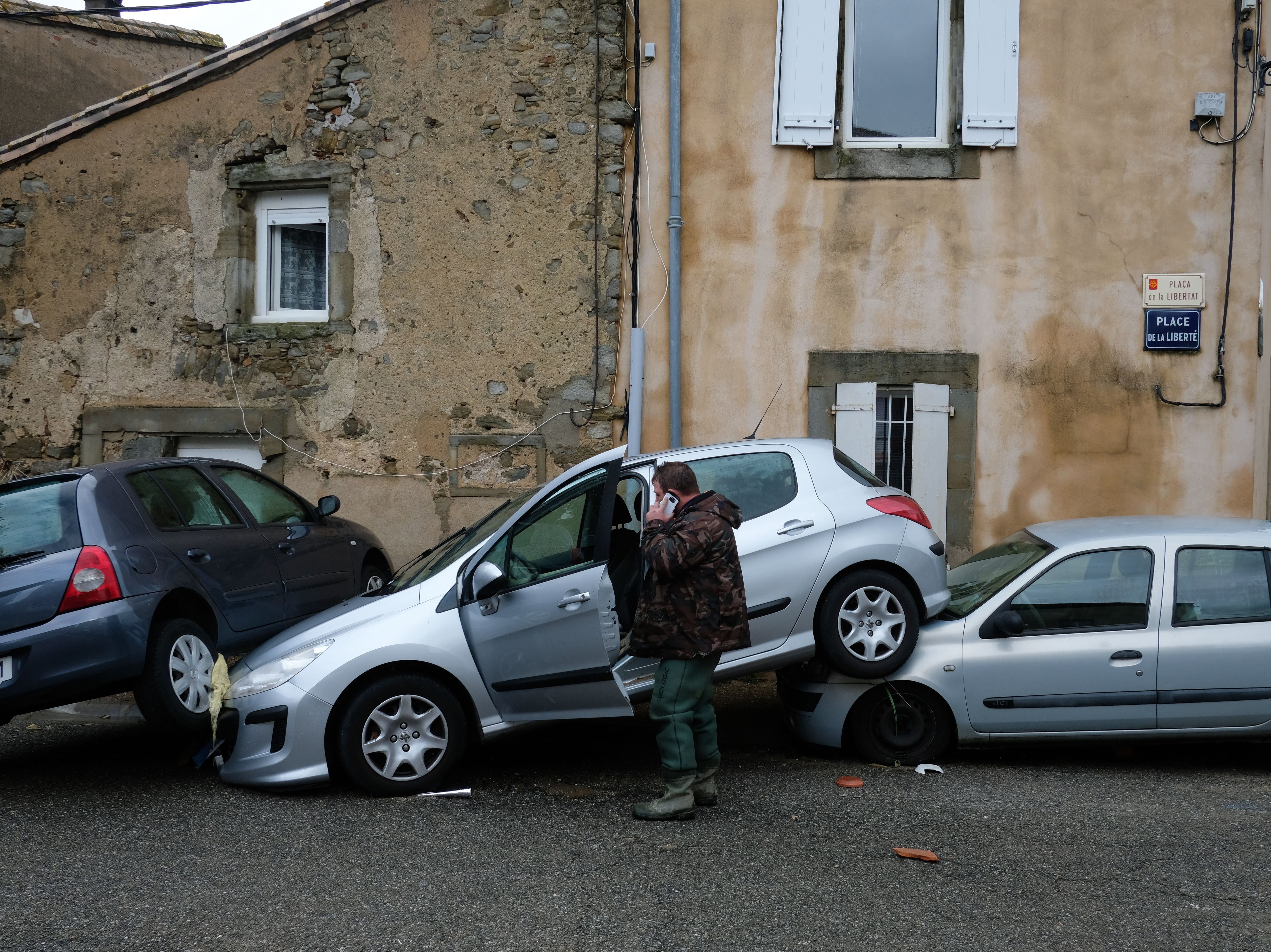 A resident looks at damaged cars piled up on following heavy rains that saw rivers bursting banks on October 15, 2018 in Villegailhenc, near Carcassone, southern France.